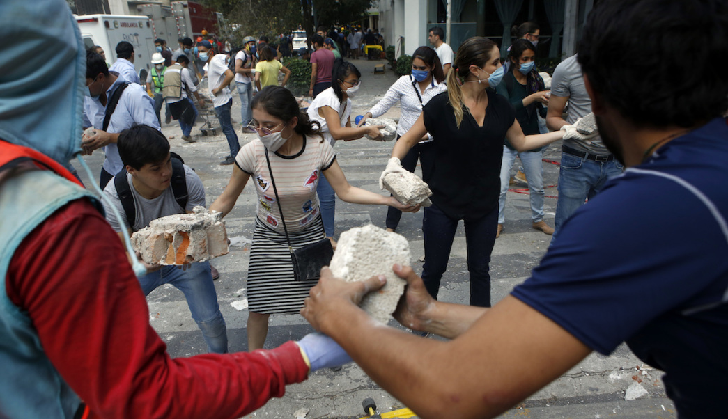 Volunteers pick up the rubble from a building that collapsed during an earthquake in the Condesa neighborhood of Mexico City, Tuesday, Sept. 19, 2017. A powerful earthquake jolted central Mexico on Tuesday, causing buildings to sway sickeningly in the capital on the anniversary of a 1985 quake that did major damage. (AP Photo/Rebecca Blackwell)